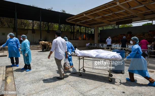 Health workers carry the body of a man who died due to coronavirus infection for cremation at Jhandewalan crematorium, on May 14, 2021 in New Delhi,...