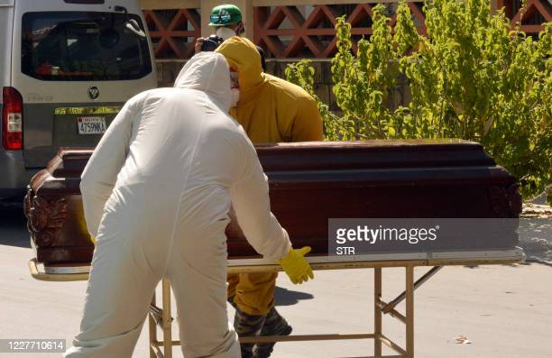 Health workers carry the coffin of a COVID-19 victim from the San Jose nursing home in Cochabamba, Bolivia, on July 20, 2020. - Ten elderly people of...