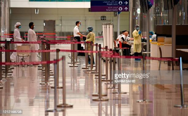 Health workers check passengers and crew who arrived in an Emirates Airlines flight from London at Dubai International Airport on May 8, 2020 amid...