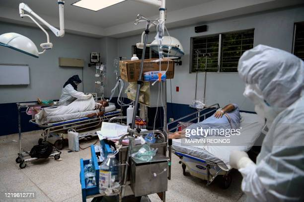 Health workers check patients infected with the novel coronavirus COVID-19 at the Intensive Care Unit of the San Rafael Hospital in Santa Tecla, La...