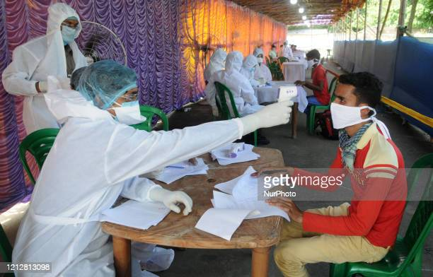 Health workers checks temperature of returnees from Bangalore and Chennai after return their home district during the national lockdown imposed by...