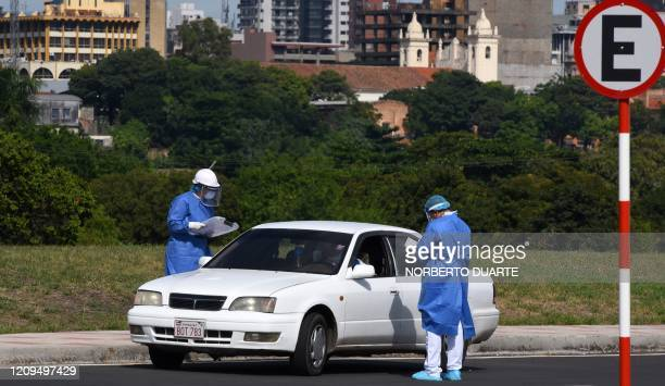Health workers conduct a test for COVID-19 on a screening-drive location at the Costanera of Asuncion, on 08 April 2020. - Paraguay is conducting...