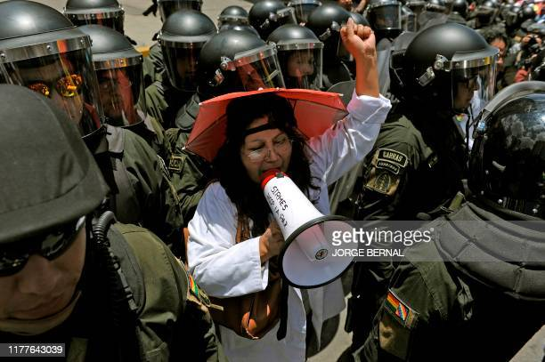 Health workers demonstrate outside the hotel where the Supreme Electoral Tribunal has its headquarters to count the election votes, in La Paz, on...