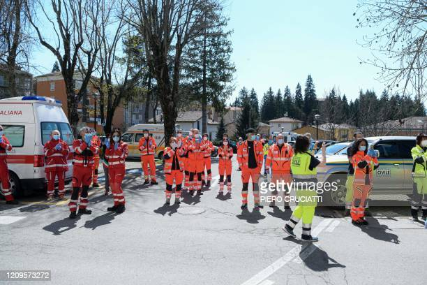 Health workers from the Civil Protection and the Italian Red Cross wearing protective gear applaud as they take part in a flash mob at the Pavullo...