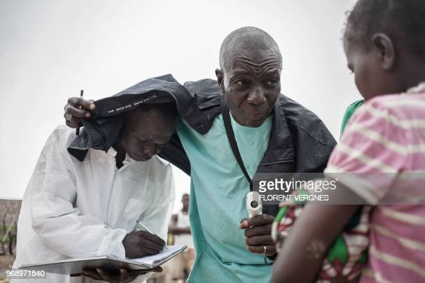 Health workers from the Ministry of Health monitor the temperature of a traveller from the Democratic Republic of Congo at each port in Bangui on...