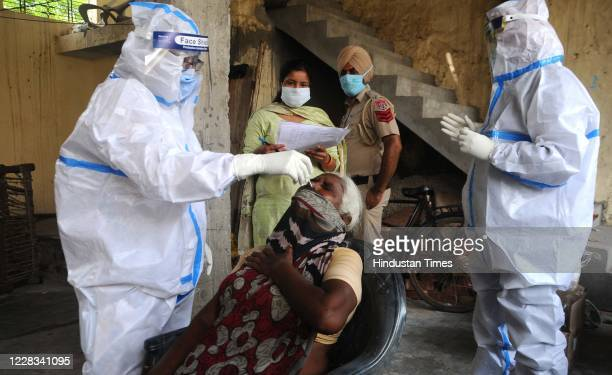 Health workers in PPE coveralls take swab samples from residents of a slum area at Rajpura Colony during a door-to-door health survey after the...