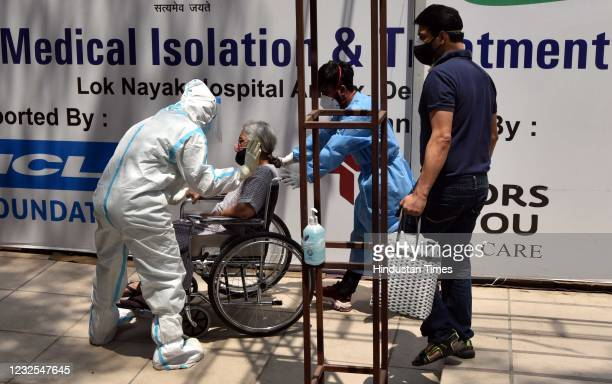 Health workers in PPE shifting a Covid-19 patient to an isolation ward at the temporary Covid Care facility attached to LNJP Hospital, at Shehnai...