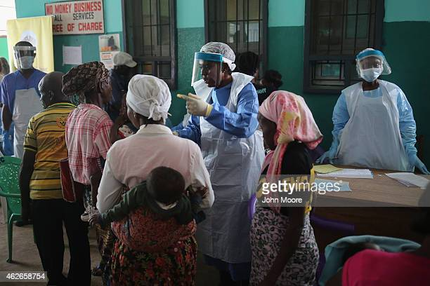 Health workers in protective clothing speak with people awaiting medical treatment in the outpatient lounge of Redemption Hospital formerly an Ebola...