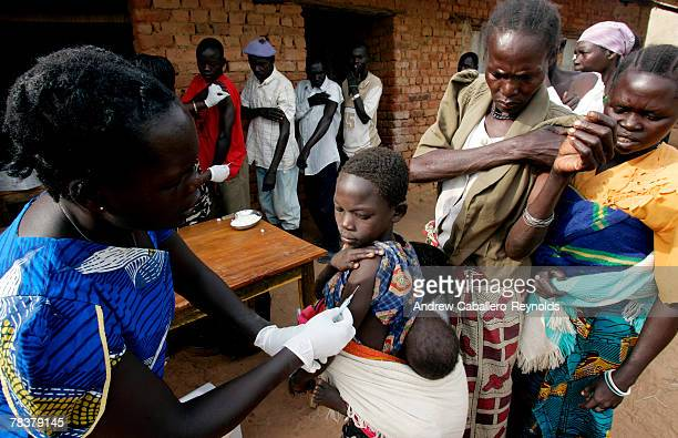 Health workers inject people with a meningitis vaccine at a field post February 14 2007 in Aura Uganda MSF conducted a massive vaccination campaign...