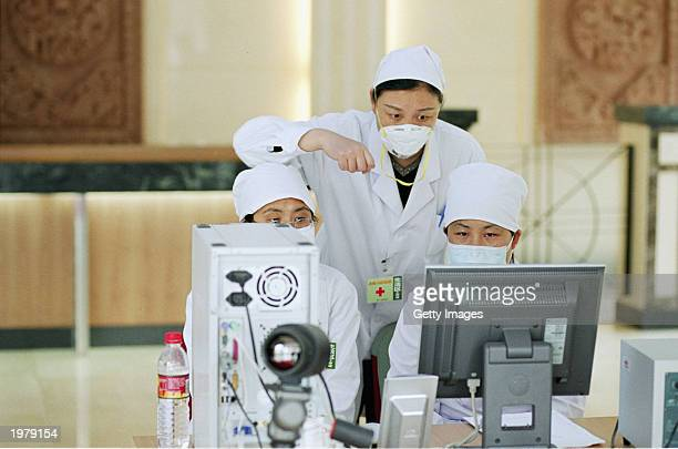 Health workers look at a screen at a facility near the newly built Xiaotangshan hospital that connects to a thermal imagery camera to monitor body...