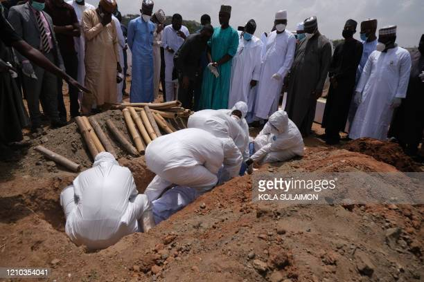 TOPSHOT Health workers lower the remains of Nigerias Chief of Staff Abba Kyari into a grave at the Gudu Cemetery in Abuja on april 18 2020 Abba Kyari...