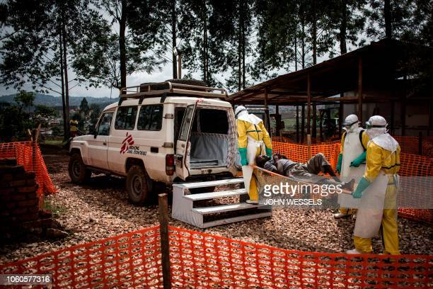 TOPSHOT Health workers move a patient to a hospital after he was cleared of having Ebola inside a MSF supported Ebola Treatment Centre on November 4...