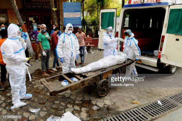 Health workers move the body of a person who died due to coronavirus on to a cart for cremation at Nigambodh Ghat crematorium in Delhi, India on June...