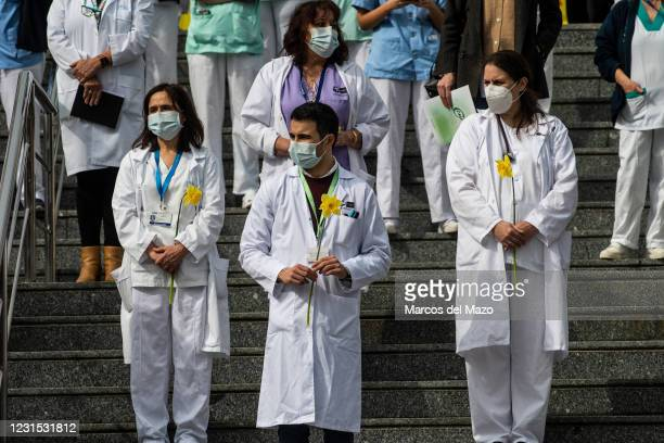 Health workers of Gregorio Marañon Hospital carrying flowers pay tribute to coronavirus victims. Approximately one year after the start of the...