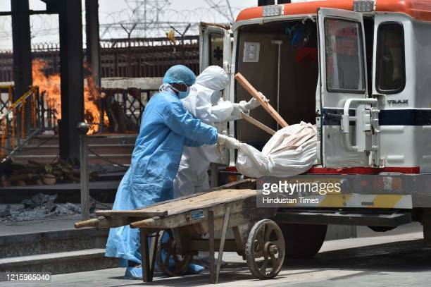 Health workers of Lok Nayak Jai Prakash Narayan Hospital in personal protective suits move the body of a woman who died of Covid-19 on a handcart for...