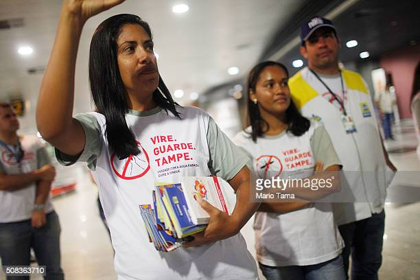Health workers pass out information on mosquito protection to people arriving in the baggage claim area at Guararapes Gilberto Freyre International...