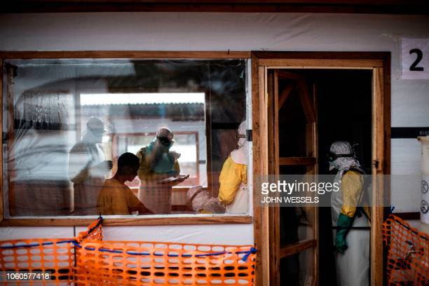 Health workers perform medical check ups on a new unconfirmed Ebola patient inside a newly build MSF supported ebola treatment centre on November 7...