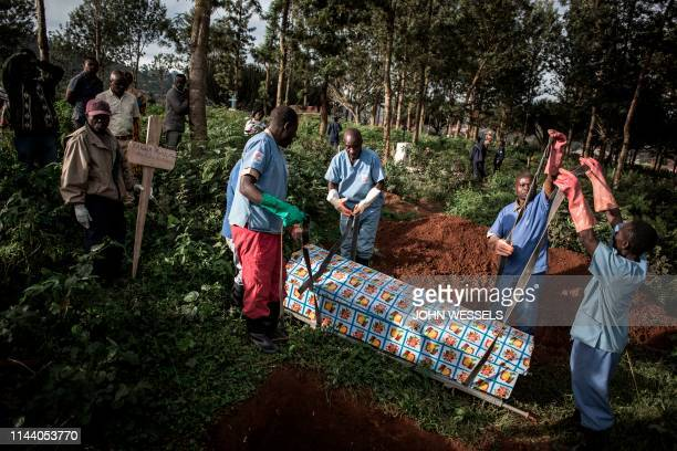 TOPSHOT Health workers prepare to bury a coffin containing a victim of the ebola virus on May 16 2019 in Butembo The city of Butembo is at the...