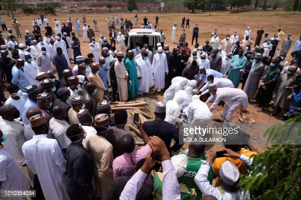 Health workers prepare to bury the remains of Nigerias Chief of Staff Abba Kyari at the Gudu Cemetery in Abuja on april 18 2020 Abba Kyari the chief...