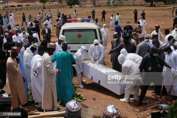 Health workers prepare to bury the remains of Nigerias Chief of Staff Abba Kyari who just died of the novel coronavirus arrived at the Gudu Cemetery...