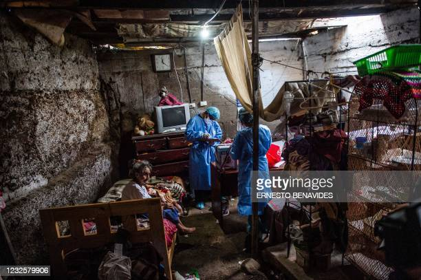 Health workers prepare to inoculate Tomasa Olguin with a dose of the Pfizer-BioNTech vaccine against COVID-19, at her house in El Agustino district...
