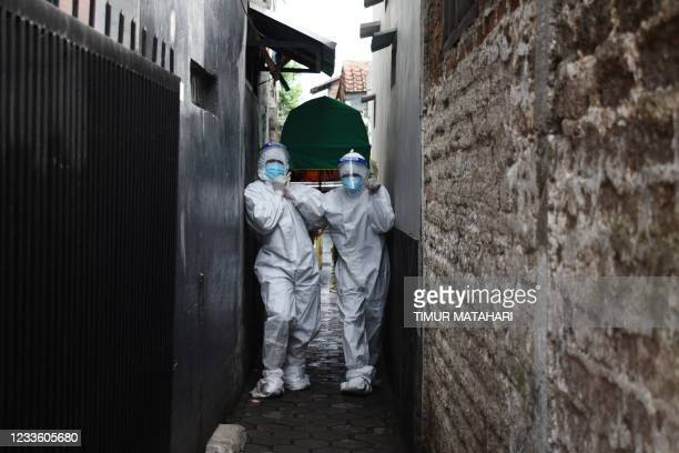 Health workers remove the body of a man who died of Covid-19 coronavirus at his Home in Bandung on June 23 as Indonesias infection rates soar and...