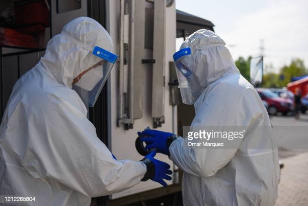 Health workers seal their suits with tape before proceding with COVID-19 tests for miners at Rybnik Regional Hospital 3 on May 8, 2020 in Rybnik,...