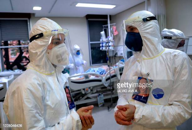 Health workers speak as a patient infected with COVID-19 is treated at the Intensive Care Unit of the Santa Casa de Misericordia Hospital in Porto...