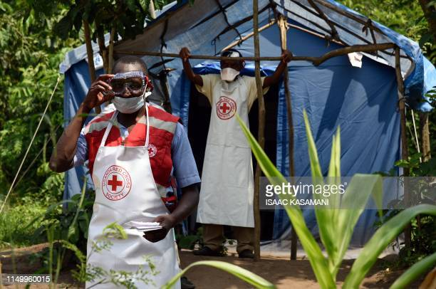 Health workers stand at a non-gazetted crossing point in the Mirami village, near the Mpondwe border check point between Uganda and the Democratic...