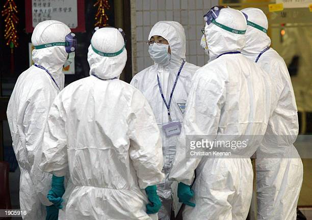 Health workers stand outside block E of Amoy Gardens on April 8, 2003 in Hong Kong. The Hong Kong government is trying to pin down the reason for the...