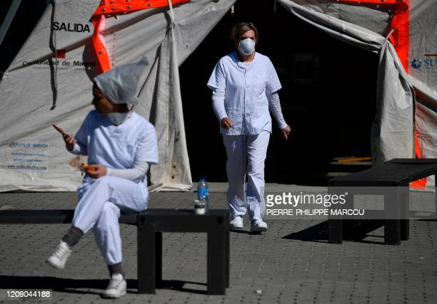 Health workers stand outside the Ifema convention and exhibition centre in Madrid on April 03 2020 where a temporary hospital for COVID19 patients is...