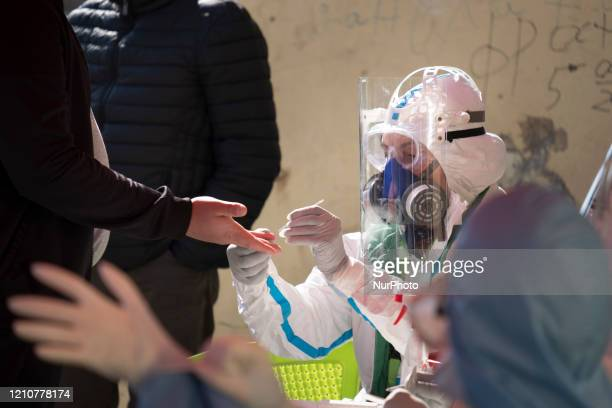 Health workers take blood to perform fast antibody tests in Fakulteta a Roma neighborhood in Sofia Bulgaria on April 23 2020 Fakulteta is one of two...