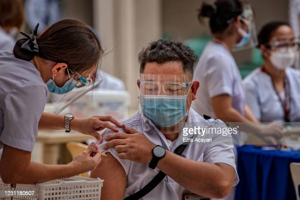 Health workers take part in a mock COVID-19 vaccination drill at the Philippine General Hospital on February 15, 2021 in Manila, Philippines....