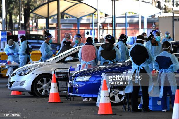 Health workers takes swab samples from residents at a Covid-19 drive-through testing clinic in Sydney on July 28, 2021.