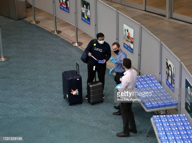 Health workers wait for passengers at COVID-19 testing area at Vancouver International Airport in Vancouver, British Columbia, Canada on February 22,...