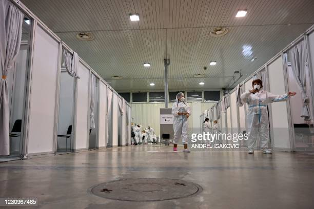 Health workers wait for people to receive a Covid-19 vaccine in Belgrade Fair turned into a vaccination centre, on February 4, 2021. - Inside the...