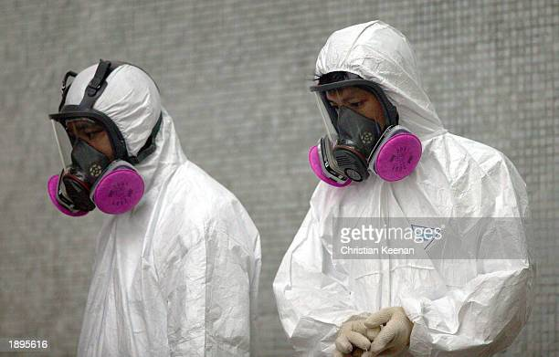 Health workers wear full protective clothing during the cleaning up operation at Amoy Gardens where over 200 residents have been infected with the...