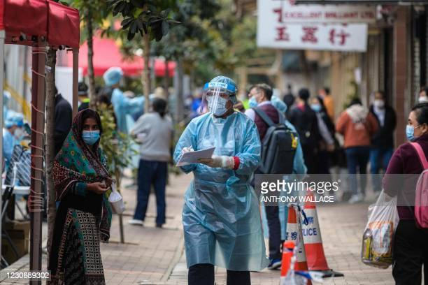 Health workers wear hazmat suits as residents of a neighbourhood queue up for a mandatory Covid-19 coronavirus test, after a spike in cases within...