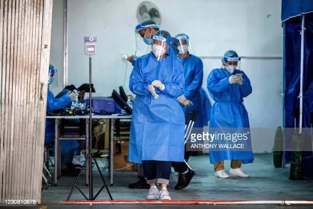 Health workers wear personal protective equipment at a COVID-19 coronavirus testing centre in Hong Kong on January 27, 2021.