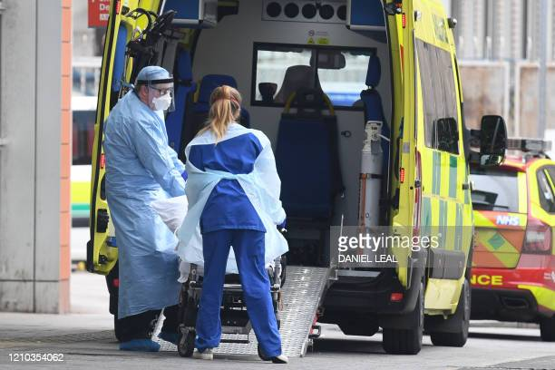 Health workers wear PPE as they transfer a patient from an ambulance into The Royal London Hospital in east London on April 18 during the novel...