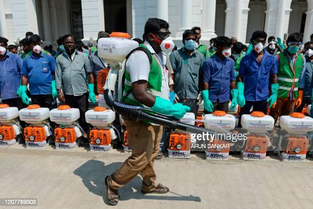 Health workers wearing facemasks amid concerns over the spread of the COVID19 novel coronavirus prepare to spray disinfectant at the corporation...