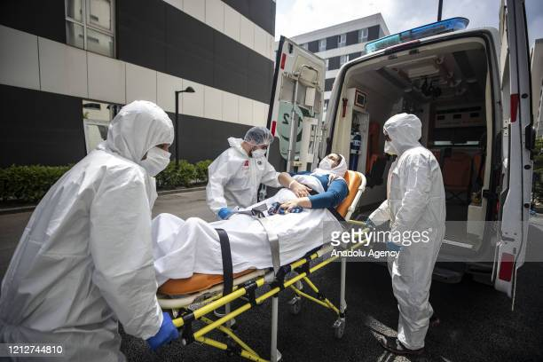 Health workers wearing full body protective suits carry a patient with suspected COVID-19 to emergency service provided for coronavirus patients at...