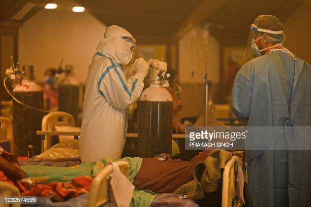 Health workers wearing personal protective equipment attends to Covid-19 coronavirus positive patients inside a banquet hall temporarily converted...
