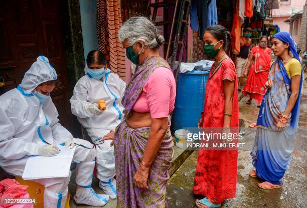 Health workers wearing Personal Protective Equipments take down contact details as they check residents during a COVID-19 coronavirus screening in...