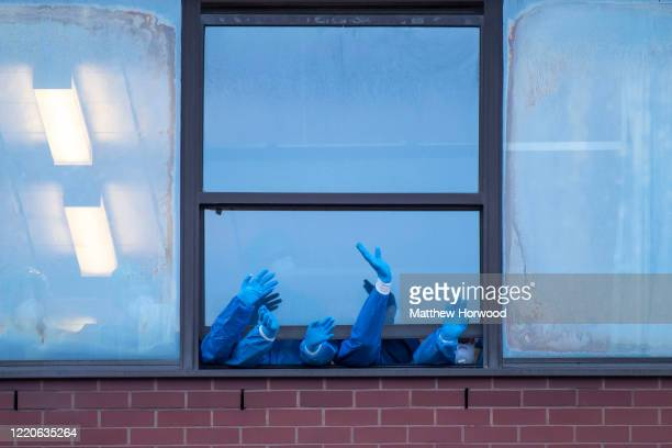 Health workers wearing PPE clap from a window at the Royal Gwent Hospital on April 23, 2020 in Newport, United Kingdom. Following the success of the...
