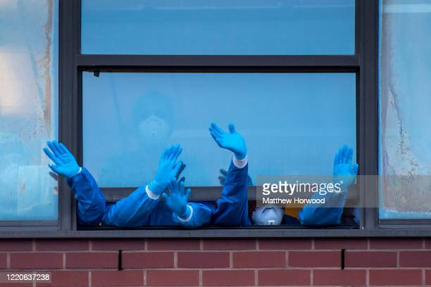 Health workers wearing PPE clap from a window at the Royal Gwent Hospital on April 23 2020 in Newport United Kingdom Following the success of the...