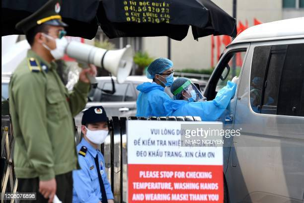 Health workers wearing protective clothing amid concerns of the spread of the COVID-19 coronavirus, check temperatures of visitors at the entrance of...