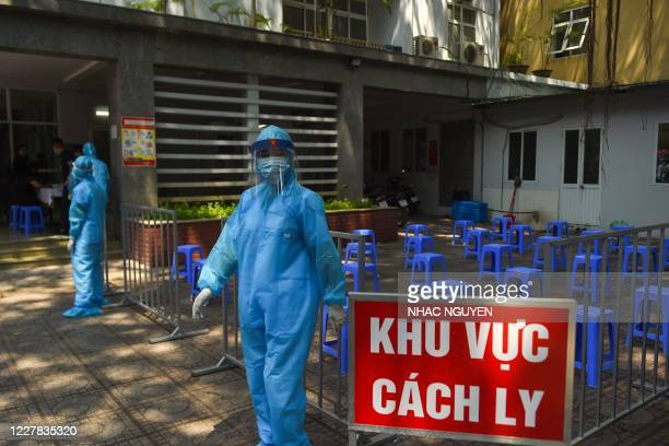 Health workers, wearing protective clothing amid fears over the spread of the COVID-19 novel coronavirus, wait for residents to arrive at a makeshift...