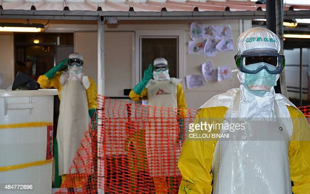 Health workers wearing protective gear gesture at the Nongo ebola treatment centre in Conakry Guinea on August 21 2015 The World Health Organization...