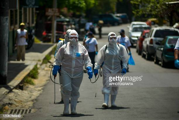 Health workers wearing protective gear perform a sanitization process on March 26, 2020 in San Salvador, El Salvador. Thirteen cases of COVID-19 have...